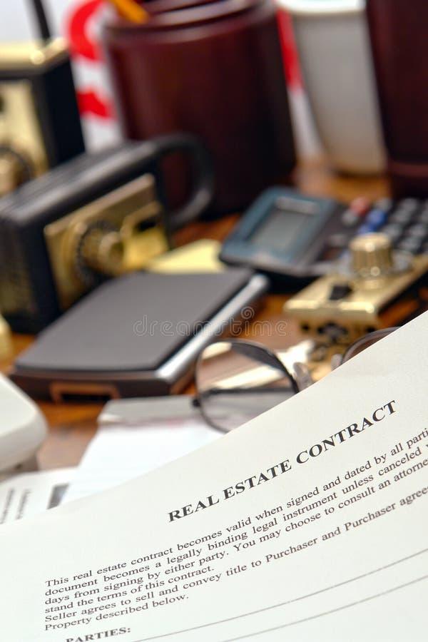 Documento del contratto del bene immobile sullo scrittorio di agente immobiliare immagini stock libere da diritti