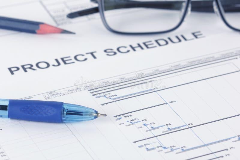 Documento del horario de proyecto con la pluma, el lápiz, eyeglases y la carta de Gantt imagenes de archivo