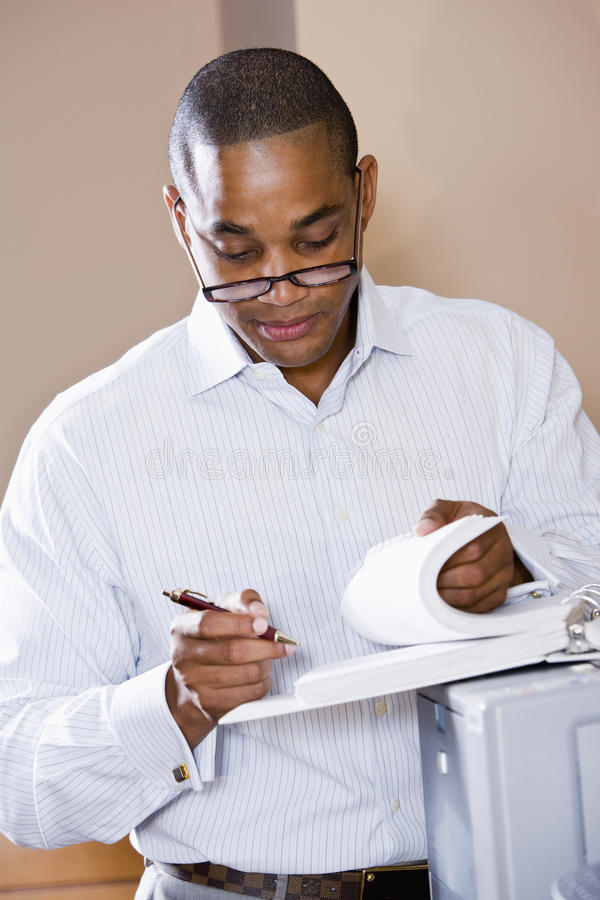 Documento della lettura dell'uomo d'affari dell'afroamericano fotografia stock libera da diritti