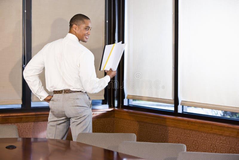 Documento della lettura dell'uomo d'affari dell'afroamericano immagine stock