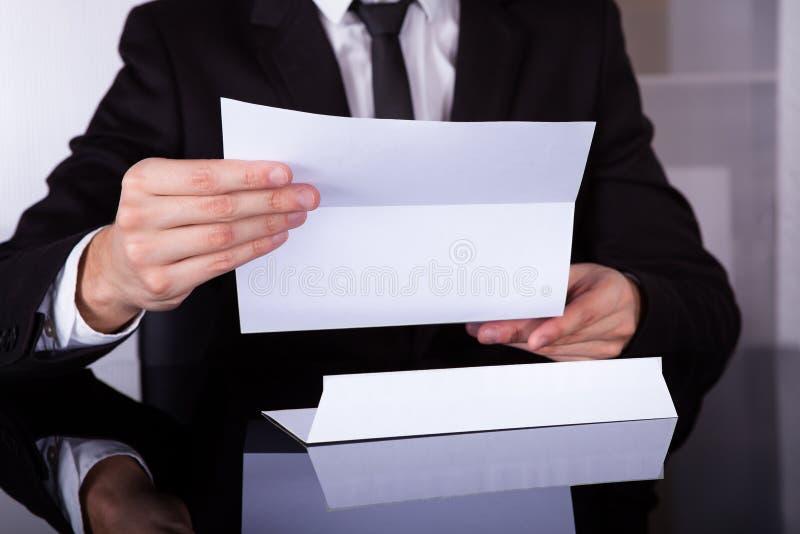 Documento della tenuta dell'uomo d'affari allo scrittorio fotografia stock libera da diritti