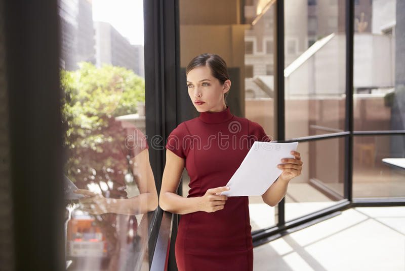 Documento della tenuta della donna di affari, guardante dalla finestra dell'ufficio fotografia stock libera da diritti