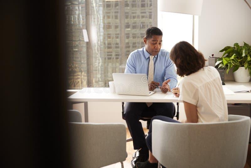 Documento di firma del cliente femminile nella riunione con il consulente finanziario maschio in ufficio fotografia stock