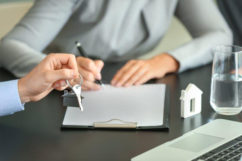 Documento di firma della donna nell'ufficio dell'agente immobiliare fotografia stock libera da diritti