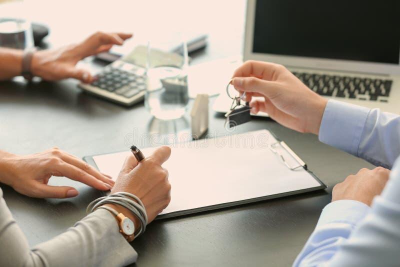 Documento di firma della donna nell'ufficio dell'agente immobiliare immagine stock