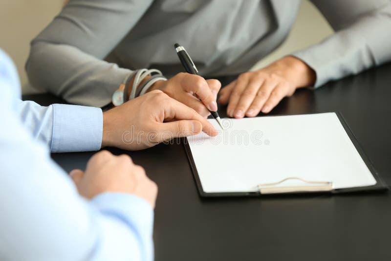 Documento di firma della donna nell'ufficio dell'agente immobiliare immagine stock libera da diritti