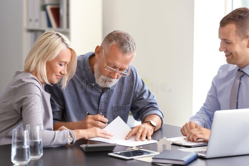 Documento di firma delle coppie mature nell'agente immobiliare in ufficio fotografie stock libere da diritti