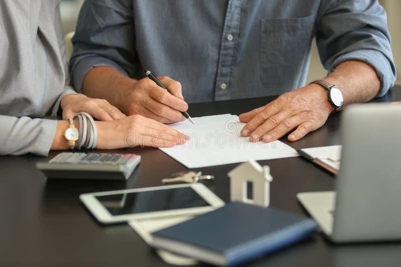 Documento di firma delle coppie mature nell'ufficio dell'agente immobiliare immagini stock
