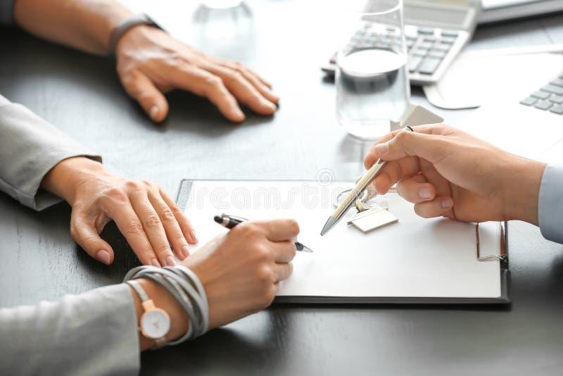 Documento di firma delle coppie mature nell'ufficio dell'agente immobiliare immagine stock libera da diritti