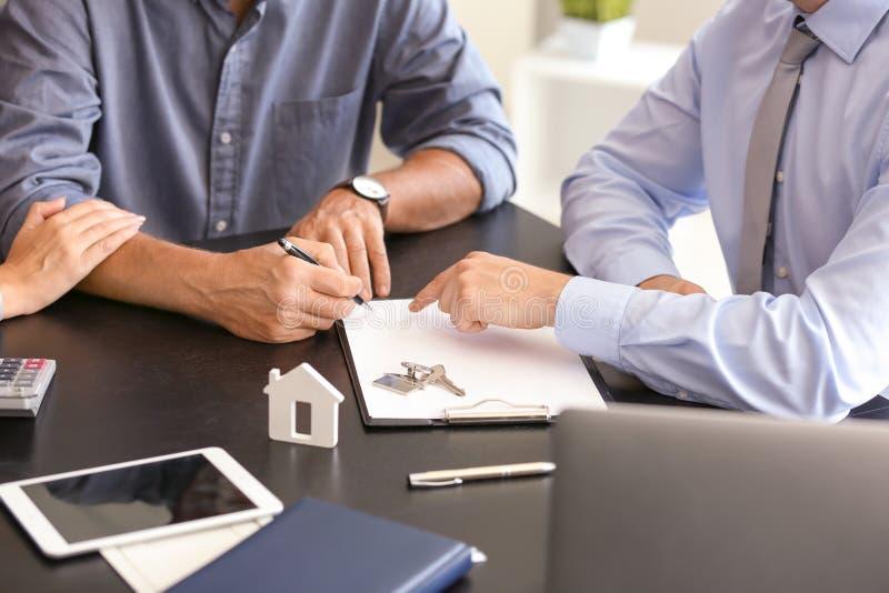 Documento di firma delle coppie mature nell'ufficio dell'agente immobiliare fotografie stock libere da diritti