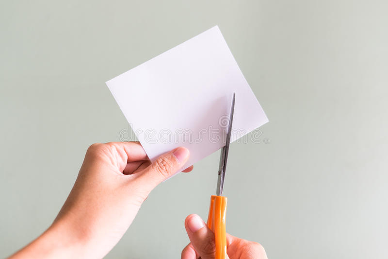Documento di taglio con le forbici immagini stock