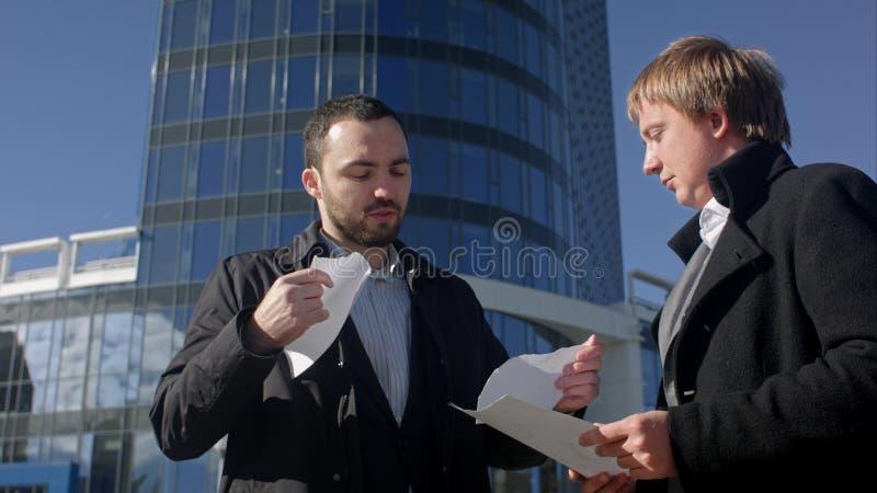 Documento en blanco del rasgón del hombre de negocios sobre el encuentro al aire libre fotografía de archivo