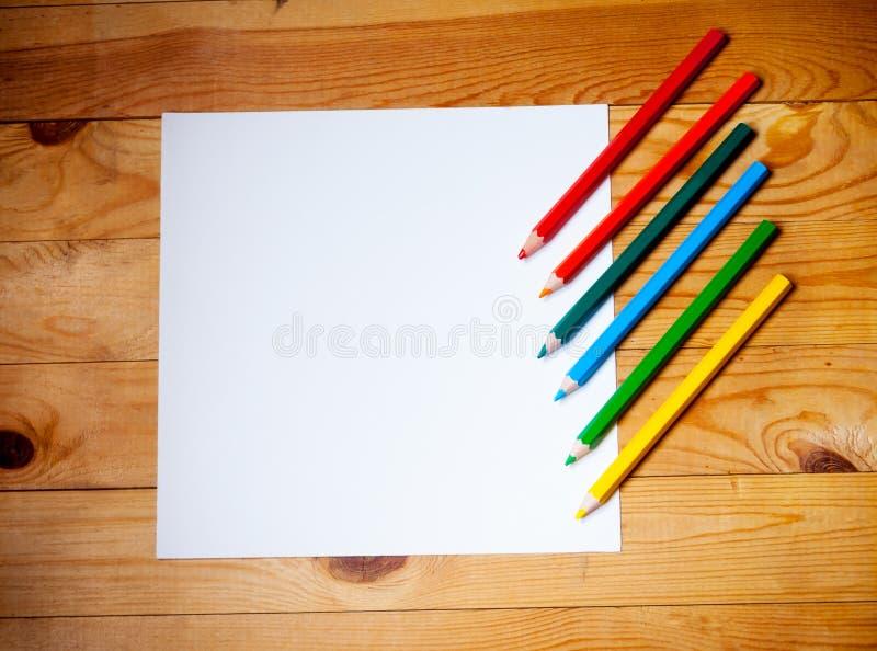 Documento en blanco y lápices coloridos sobre la tabla de madera foto de archivo