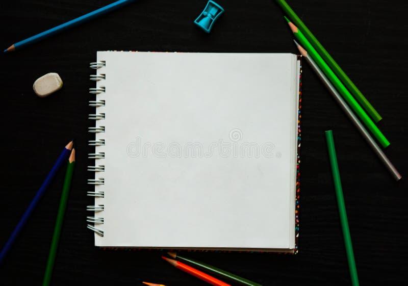 Documento en blanco y lápices coloridos sobre la tabla de madera oscura fotos de archivo