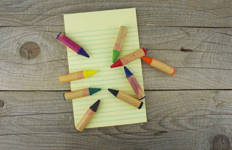 Documento en blanco y lápices coloridos sobre la tabla de madera Visión desde fotografía de archivo libre de regalías