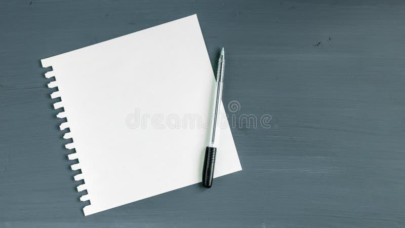 Documento en blanco y pluma sobre fondo de madera gris imagen de archivo