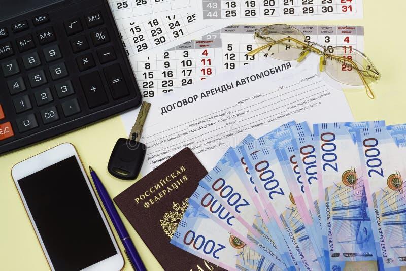 Documento en el contrato de alquiler del Ruso-coche, el pasaporte ruso, la calculadora, el dinero y el smartphone fotos de archivo libres de regalías