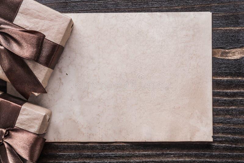 Documento encajonado lleno de los regalos sobre concepto del día de fiesta del tablero de madera del vintage imagen de archivo libre de regalías