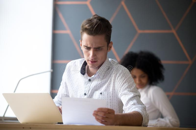 Documento masculino de las estadísticas de la lectura del empleado en oficina imagen de archivo