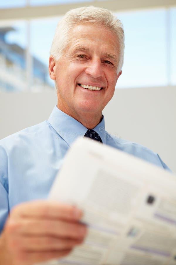 Documento mayor feliz de la lectura del hombre de negocios fotografía de archivo