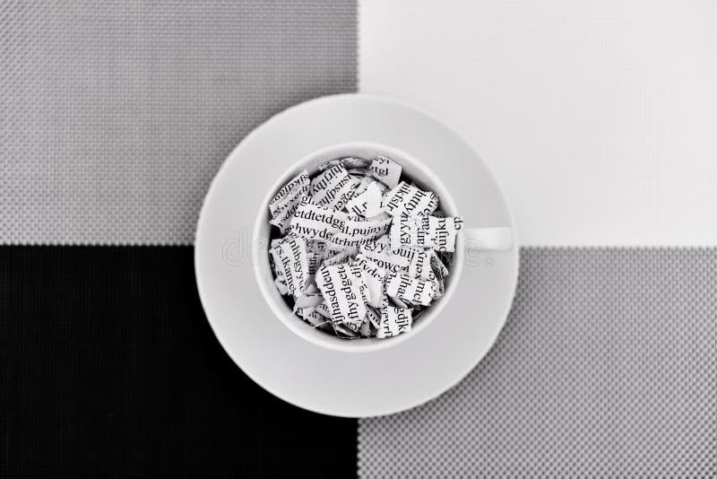 Documento quebrado en una taza de café foto de archivo