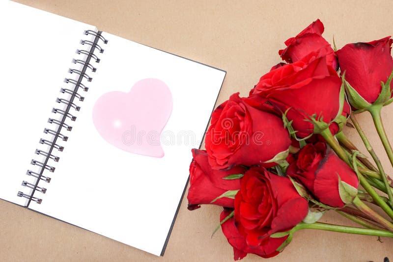 Documento rosado del corazón sobre el cuaderno abierto con las rosas rojas fotografía de archivo libre de regalías