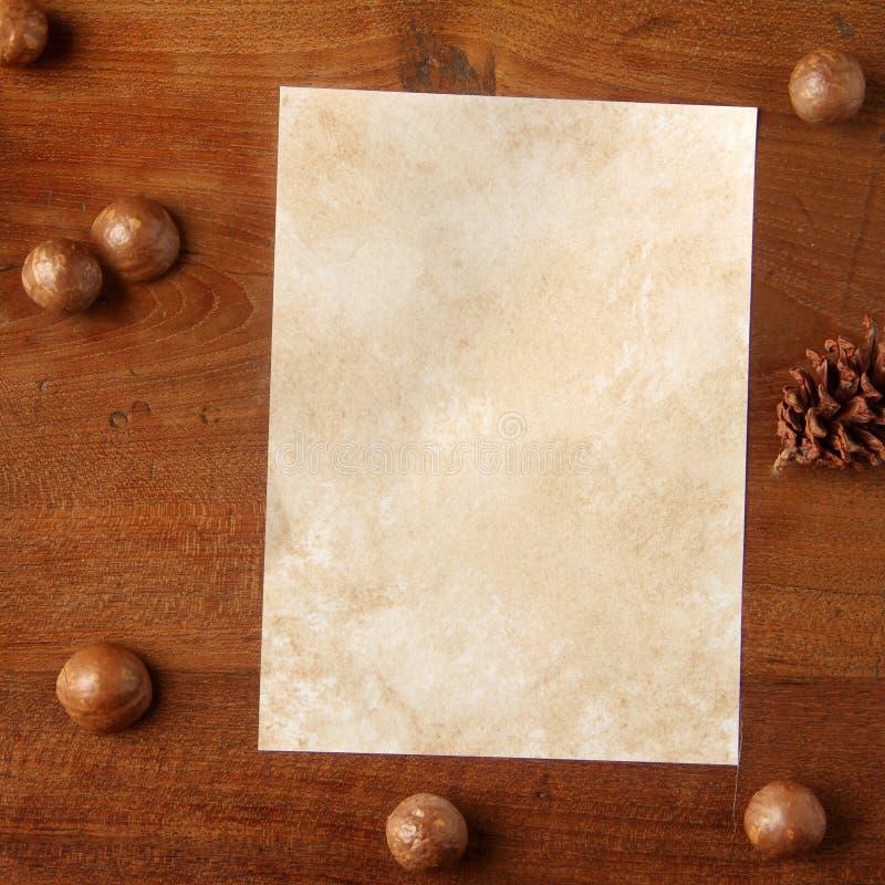Documento sobre tablero del teakwood con la nuez de la almendra de la araucaria de los conos fotos de archivo