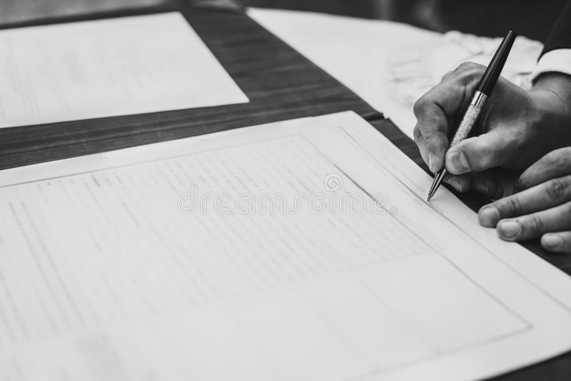 Documento ufficiale o contratto di firma dell'uomo d'affari Registro di firma di nozze dello sposo alla moda con la penna di luss fotografie stock