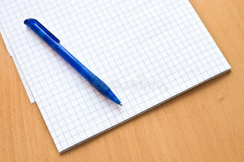 Documento y pluma de la rejilla sobre la tabla fotografía de archivo