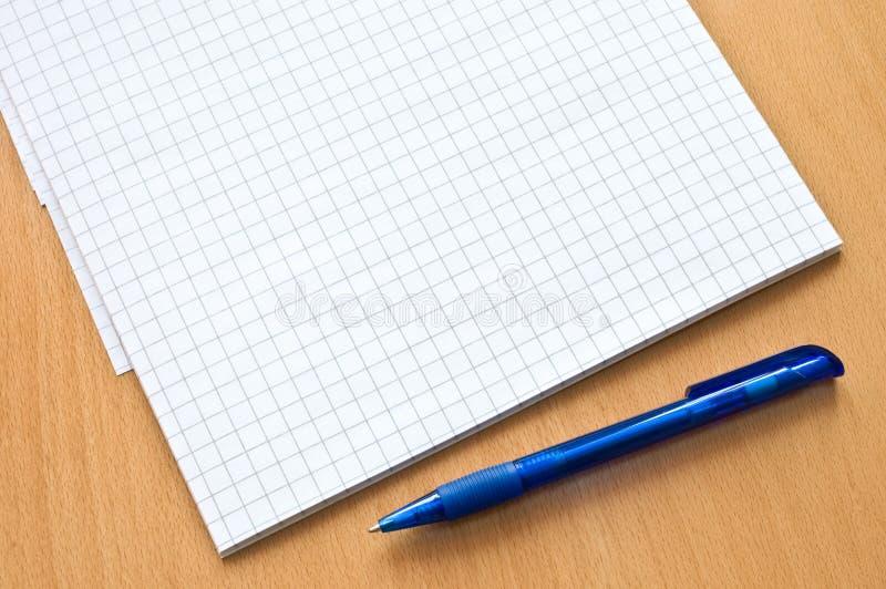 Documento y pluma de la rejilla sobre la tabla fotos de archivo