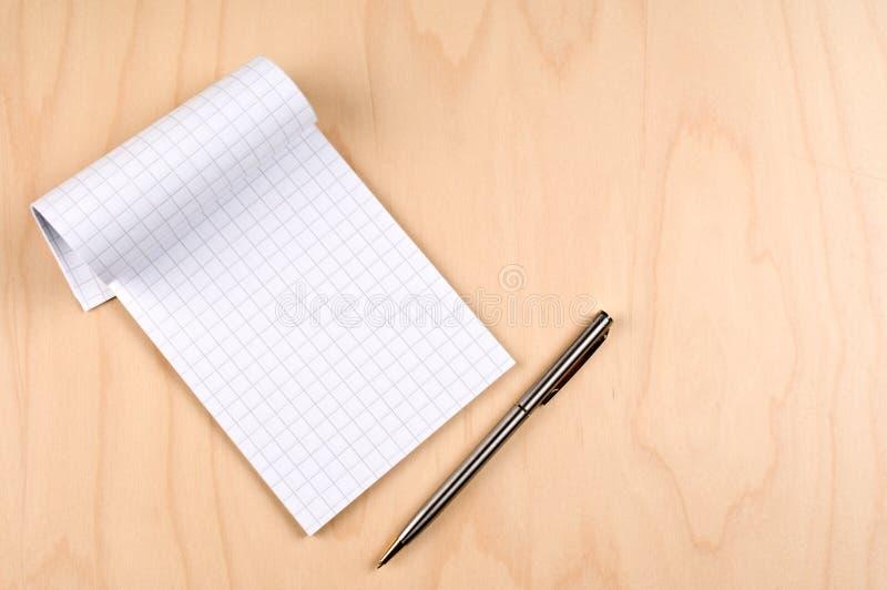 Documento y pluma de la rejilla sobre la tabla imágenes de archivo libres de regalías
