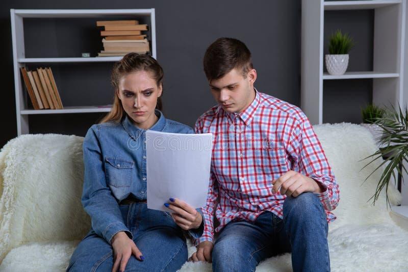 Documentos da leitura dos pares que sentam-se no sof? em casa fotografia de stock