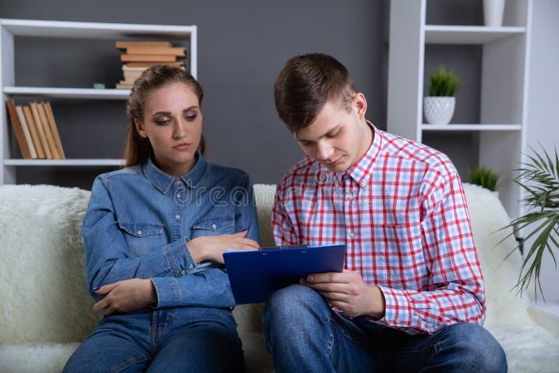 Documentos da leitura dos pares que sentam-se no sof? em casa foto de stock royalty free
