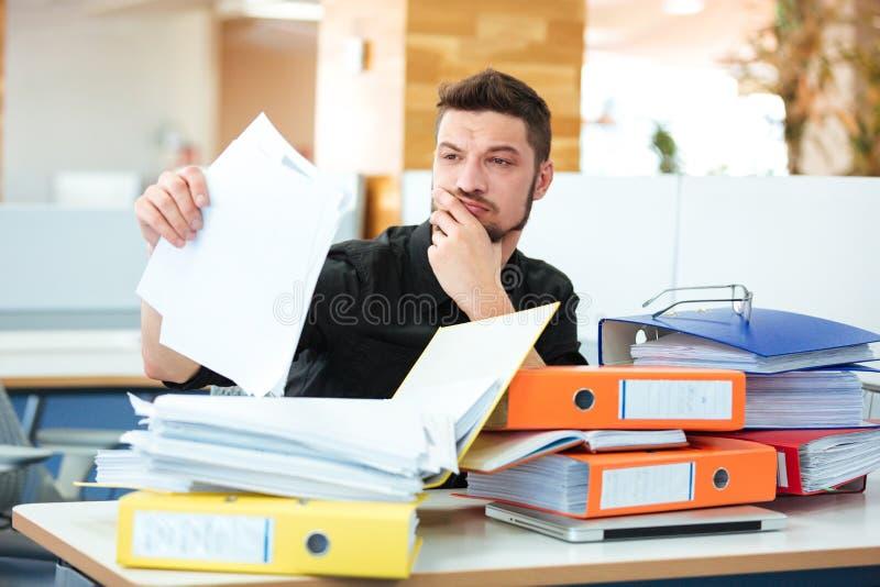 Documentos de la lectura del hombre de negocios en oficina foto de archivo