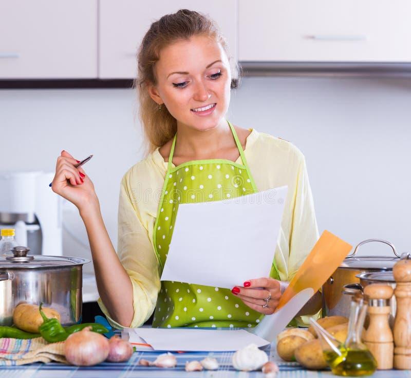 Documentos de relleno del ama de casa en la cocina fotografía de archivo libre de regalías