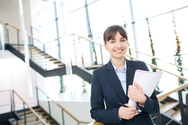 Documentos de Smiling While Holding de la empresaria contra escaleras imagenes de archivo