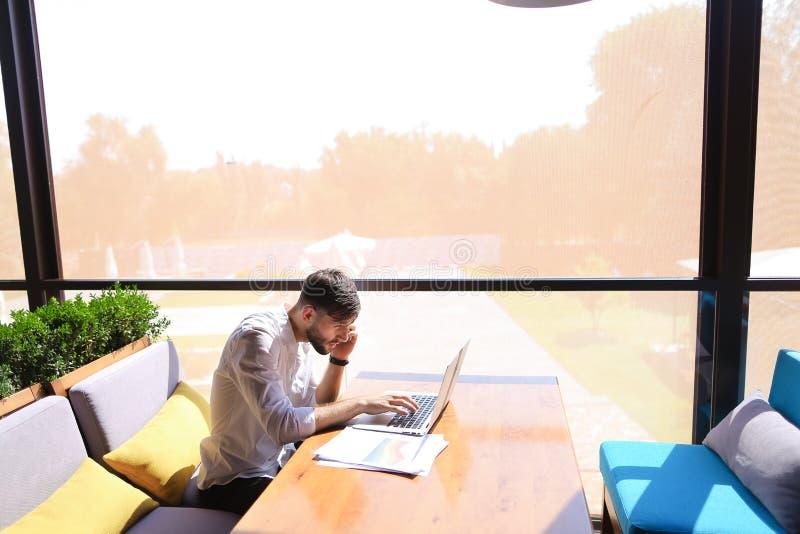 Documentos prósperos de la lectura del encargado de ventas, usando el ordenador portátil en el tabl fotos de archivo libres de regalías