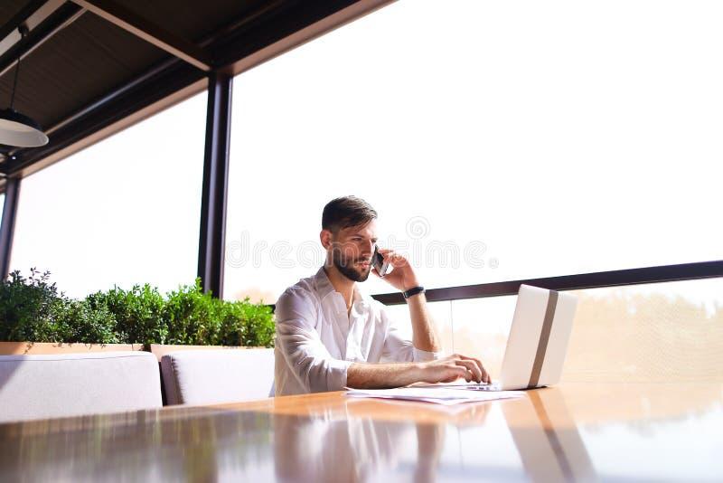 Documentos prósperos de la lectura del encargado de ventas, usando el ordenador portátil en el tabl foto de archivo libre de regalías