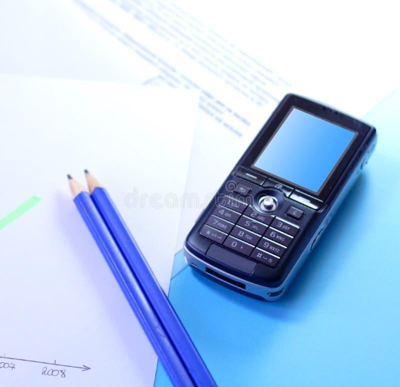Documentos y teléfono móvil imagen de archivo libre de regalías