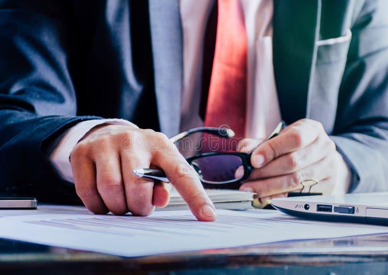 documents d'entreprise sur la table de bureau avec le diagramme financier de smartphone et de graphique et les gens d'affaires tr images stock