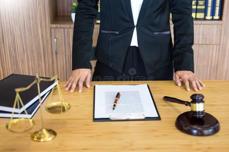 Documents de lecture de juge d'avocat au bureau dans la salle d'audience travaillant au fond en bois de bureau poids d'or de mart photographie stock