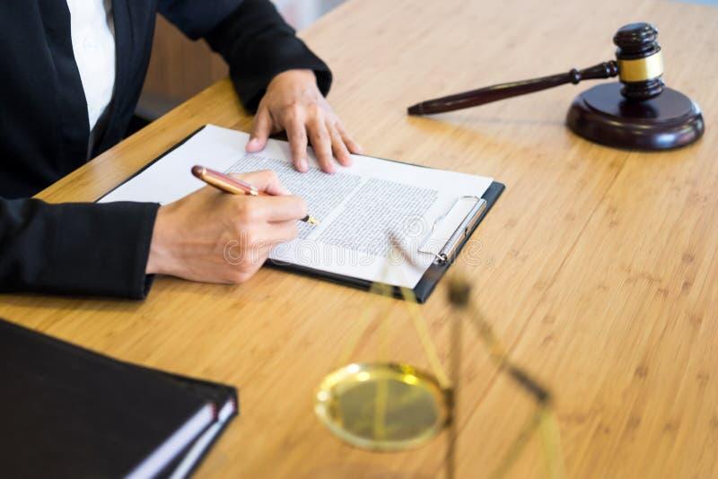 Documents de lecture de juge d'avocat au bureau dans la salle d'audience travaillant au fond en bois de bureau poids d'or de mart photographie stock libre de droits