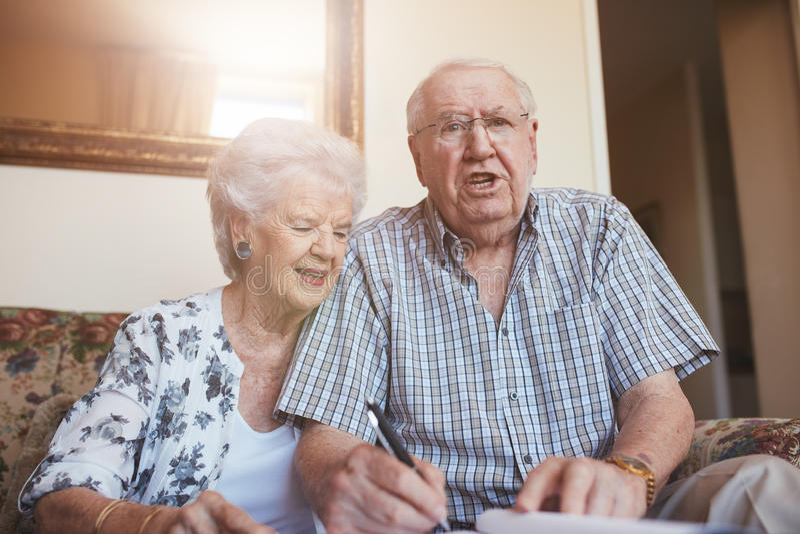 Documents de signature de couples pluss âgé tout en se reposant à la maison photos libres de droits