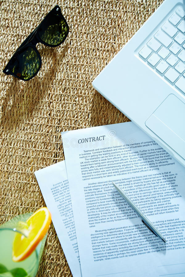 Documents and objects. Image of business contract with pen, laptop, cocktail and sunglasses near by royalty free stock images
