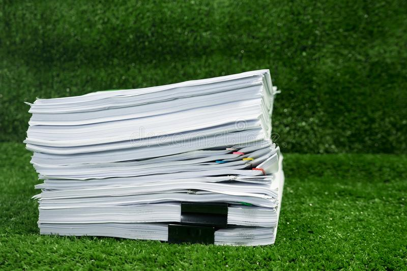 Documents pile on grass in concept save Earth stock photography