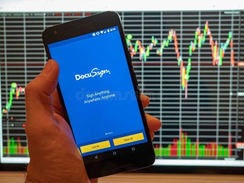 DocuSign APP mobile s'est tenu devant un diagramme de cours des actions d'actions sur une Co photographie stock libre de droits