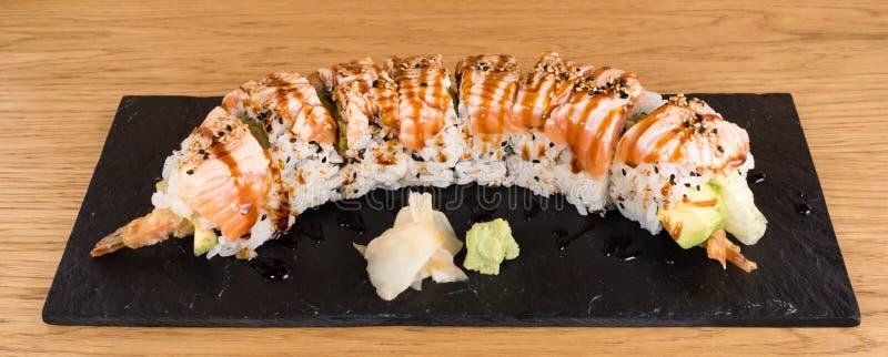 Dodatek specjalny Uramaki, ry? rolka faszeruj?ca z krewetkowym tempura, zielona sa?atka, avocado, zakrywaj?cy z piec na grillu ?o zdjęcia stock