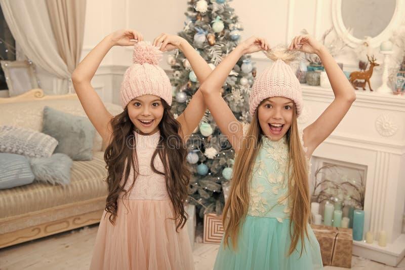 Dodatek zimowy. Dzieci noszą kapelusze dziane. Dziewczyny długie włosy uśmiechnięte twarze na drzewie świątecznym. Dzieci obraz stock