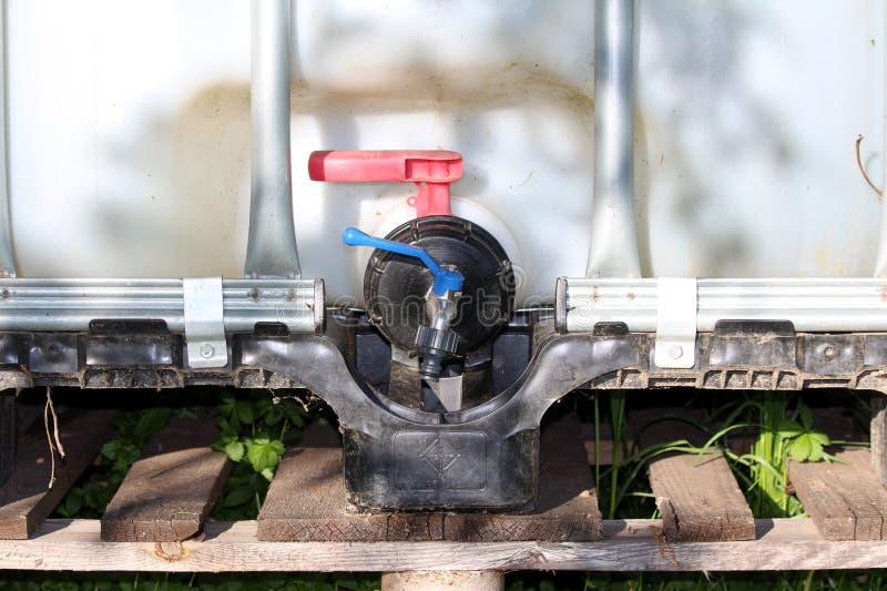 Dodatkowa mała klapa dodawał średni masowy zbiornik lub IBC plastikowy zbiornik wodny z metal klatką stawia dalej drewnianego bar fotografia stock