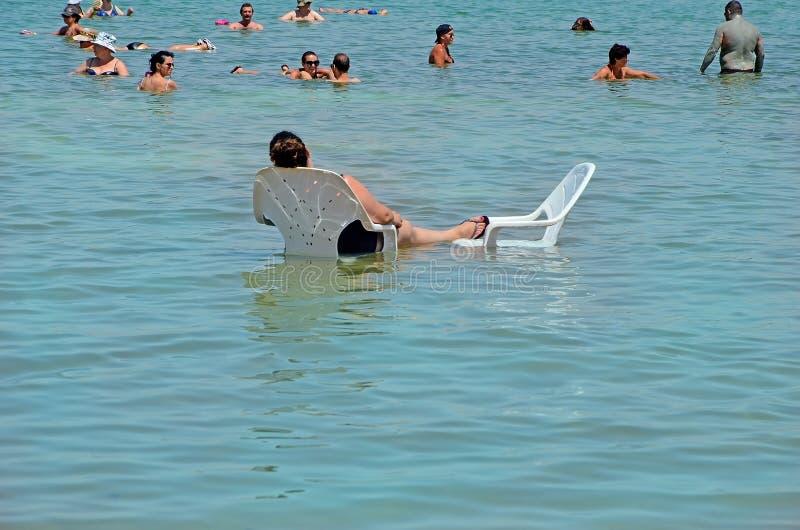 Dode overzees, Israël - 31 MEI 2017: de mensen op stoelen ontspannen en zwemmen in het water van het Dode Overzees in Israël toer royalty-vrije stock afbeelding